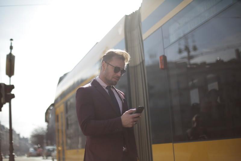 Ein Geschäftsmann benutzt ein mobiles Gerät unterwegs, um Mobilität zu verdeutlichen, während im Hintergrund eine Straßenbahn vorbeifährt.