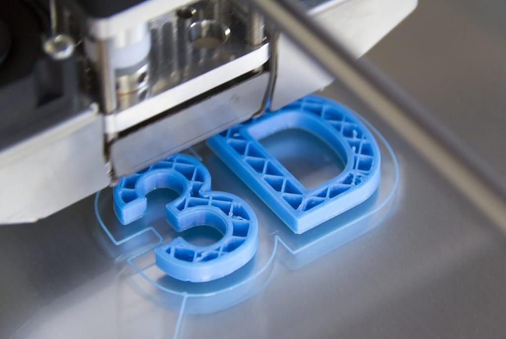 Das Bild zeigt die Buchstaben 3 und D, wie sie als plastischer Gegenstand mit einem 3D-Drucker gedruckt werden.