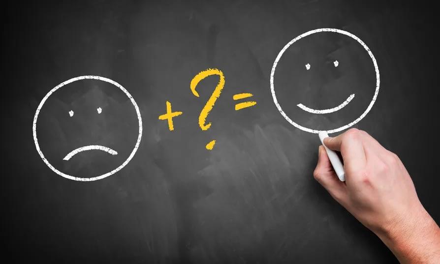 Eine auf eine Tafel gezeichnete Formel: Ein trauriger Smiley plus ein Fragezeichen ergeben sich glücklichen Smiley