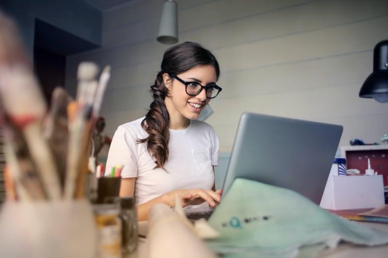 Eine Frau sitzt zufrieden vor Ihrem benutzerfreundlichen Laptop