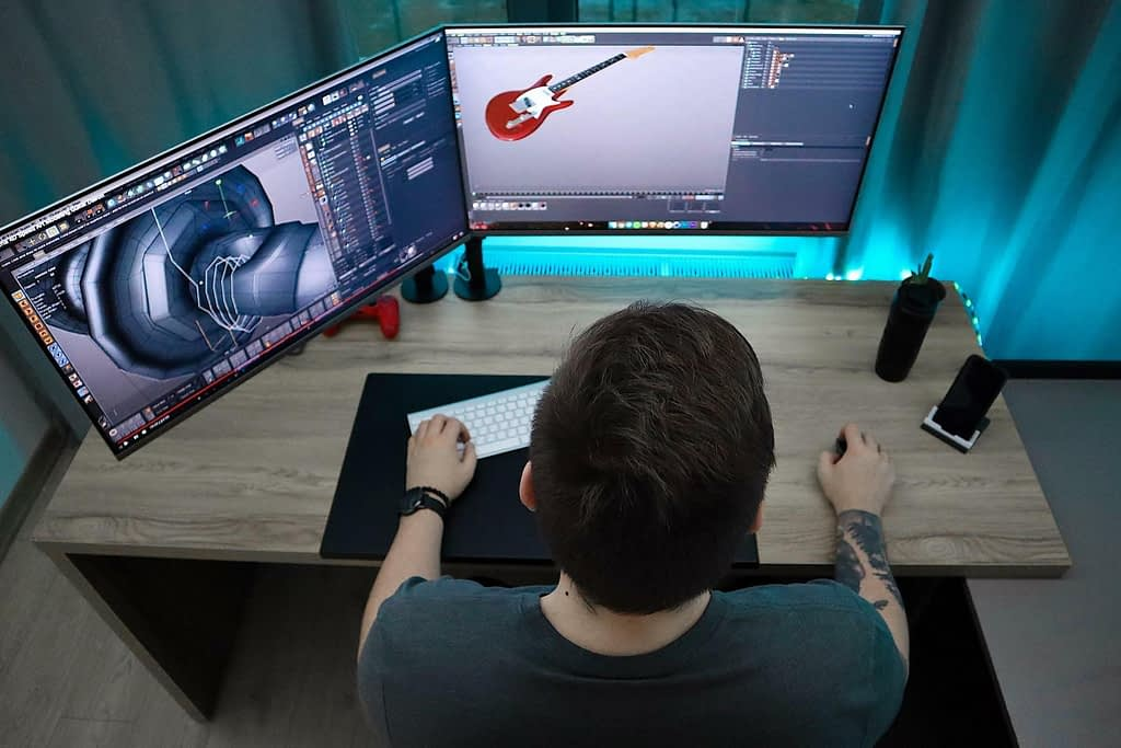 Ein Schreibtisch mit zwei PC Bildschirmen, an denen mit einer CAD Software 3D Modelle bearbeitet werden.